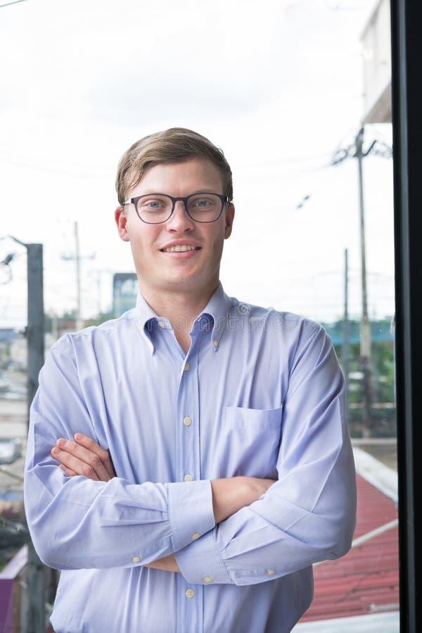 El retrato del hombre de negocios con los brazos cruzó en la oficina hombre joven s foto de archivo