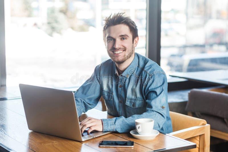 El retrato del hombre de negocios joven barbudo alegre hermoso en camisa de los tejanos se está sentando en café y mensaje que me imagen de archivo libre de regalías