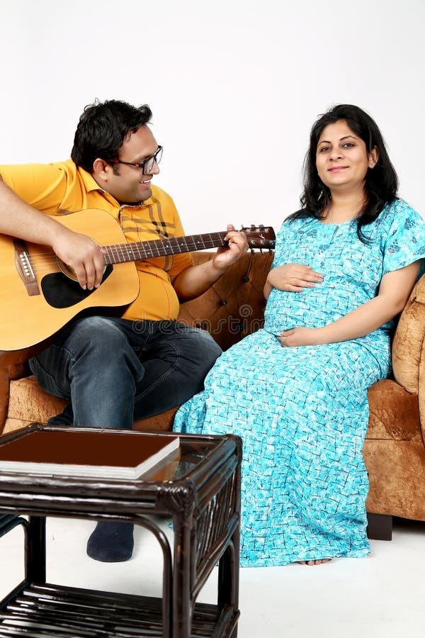 El retrato del hombre está tocando la guitarra a su esposa embarazada imagen de archivo libre de regalías