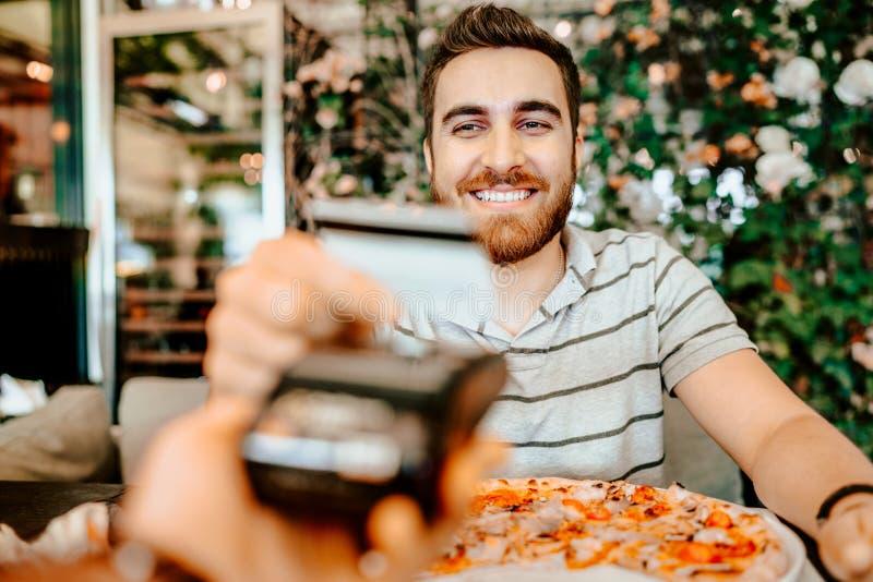 El retrato del hombre feliz que paga el almuerzo con la tarjeta de crédito, se cierra encima de los detalles foto de archivo libre de regalías