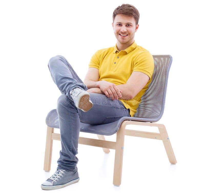 El retrato del hombre feliz sonriente se sienta en la silla de la oficina aislada en blanco imagen de archivo