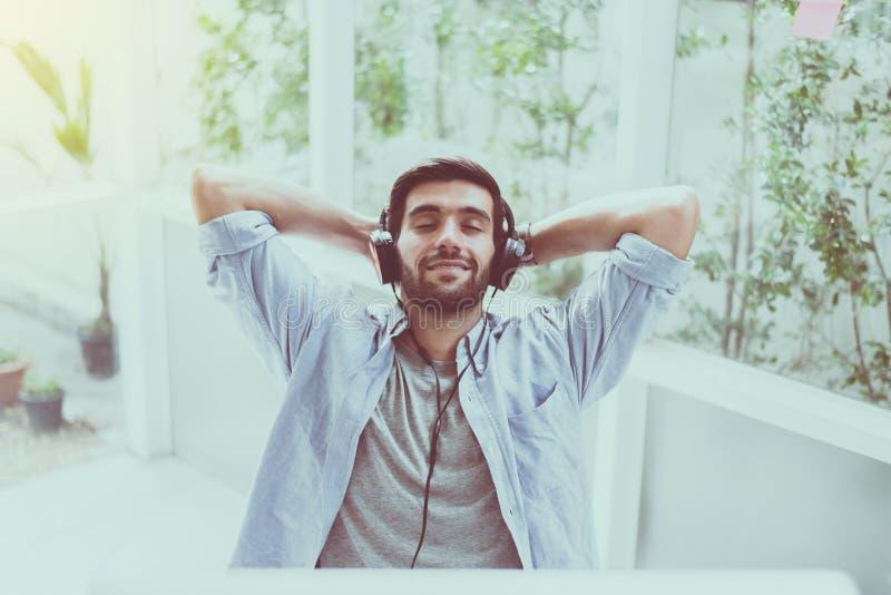 El retrato del hombre hermoso con la barba usando el auricular y de escuchar la música en casa, felices y de la sonrisa, relajan  fotos de archivo libres de regalías