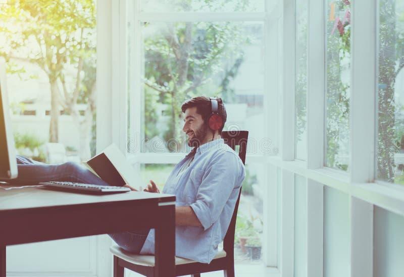 El retrato del hombre hermoso con el libro de lectura de la barba y el escuchar la música en línea en el espacio coworking, feliz foto de archivo