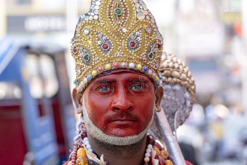 El retrato del hombre indio con maquillaje de la deidad hindú Hanuman, dios del mono entretiene a gente en la calle en Rishikesh, foto de archivo libre de regalías