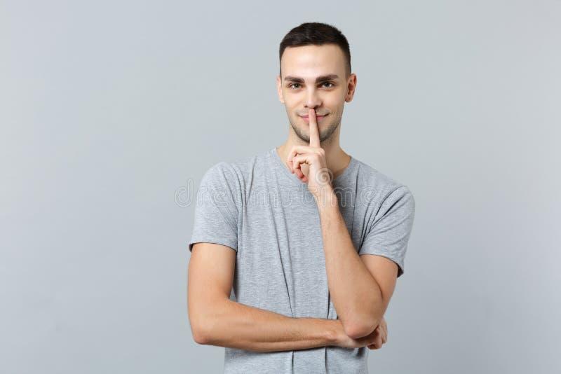 El retrato del hombre joven atractivo en ropa casual que dice silencio sea reservado con el finger en gesto de los labios shhh ai imagenes de archivo