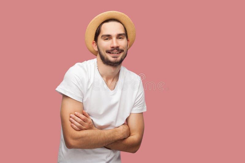 El retrato del hombre joven barbudo acertado feliz en la camisa blanca con la situación del sombrero, cruzó los brazos y la mirad foto de archivo