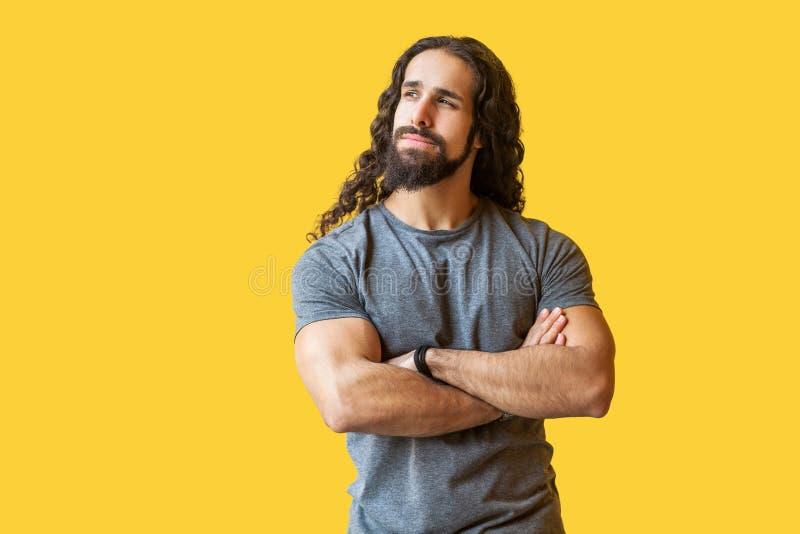 El retrato del hombre joven barbudo pensativo con el pelo rizado largo en la situación gris de la camiseta, cruzó las manos, mira fotos de archivo libres de regalías