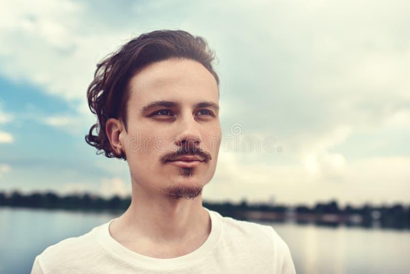 El retrato del hombre joven disfruta de una hermosa vista y de miradas en la distancia cerca de un lago y de un bosque Verano Pri fotografía de archivo