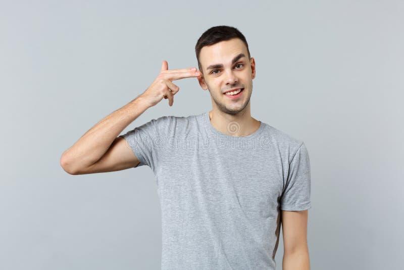 El retrato del hombre joven sonriente en ropa casual señala los fingeres para dirigir como si él se tire alrededor aislado en gri imagen de archivo