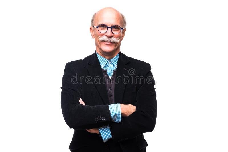 El retrato del hombre mayor serio está presentando con las manos cruzadas aisladas en el fondo blanco fotos de archivo