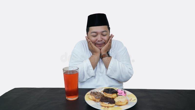El retrato del hombre musulmán gordo con el casquillo principal o el songkok ruega antes come y bebe para el ayuno de la rotura d fotografía de archivo libre de regalías