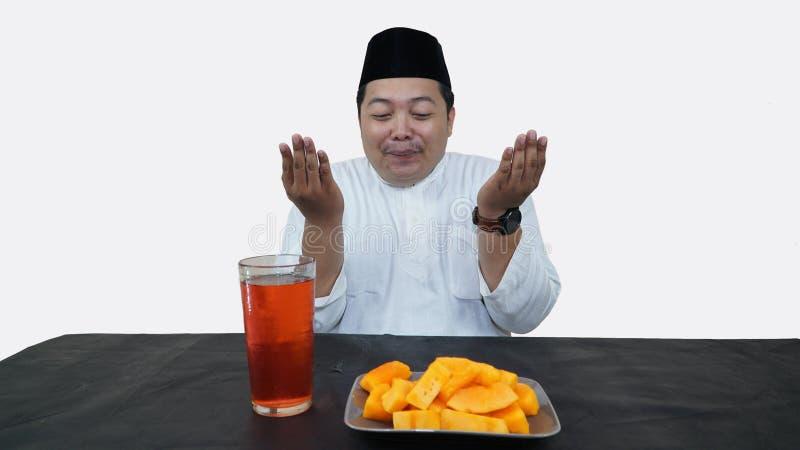 El retrato del hombre musulm?n gordo con el casquillo principal o el songkok ruega antes come y bebe para el ayuno de la rotura d imagen de archivo