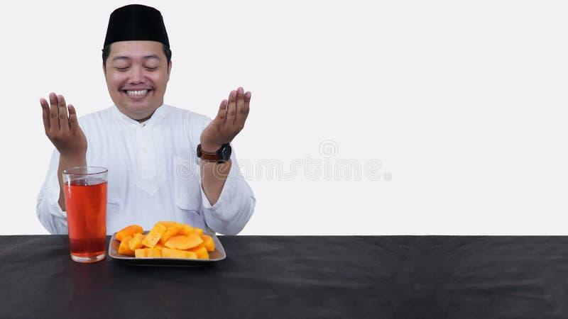 El retrato del hombre musulm?n gordo con el casquillo principal o el songkok ruega antes come y bebe para el ayuno de la rotura d imagen de archivo libre de regalías