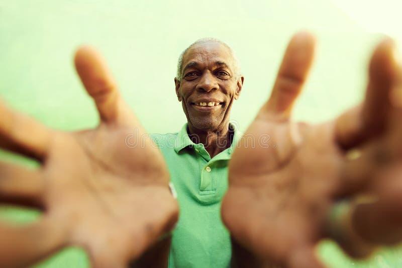 El viejo hombre africano con las manos y los brazos se abren, abrazando la cámara imagen de archivo