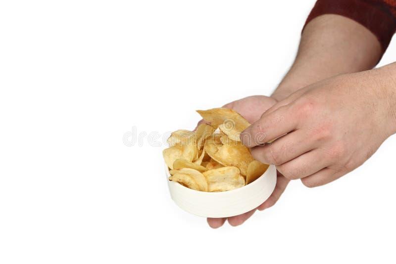El retrato del hombre se está sosteniendo en las patatas fritas de una mano en el cuenco y la otra mano está escogiendo microproc imagenes de archivo