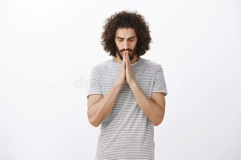 El retrato del individuo hispánico de creencia enfocado con la barba y el peinado afro, ojos de cierre, llevando a cabo las manos imagenes de archivo
