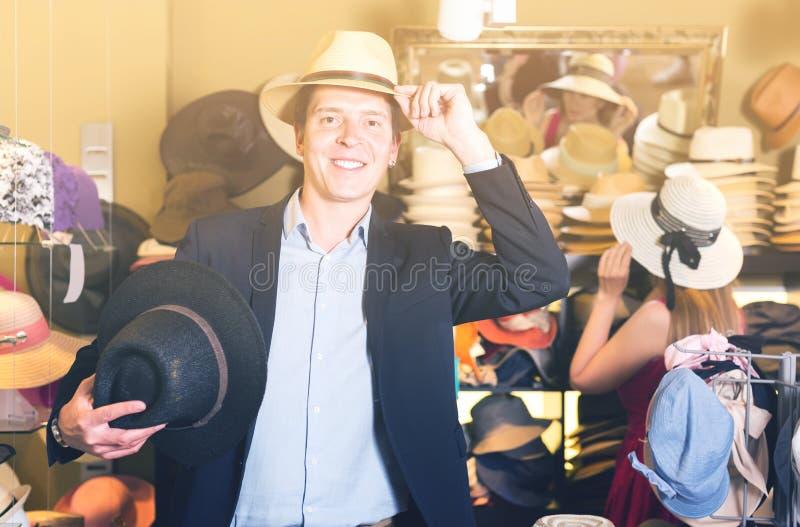 El retrato del individuo joven sonriente intenta encendido el sombrero del cubo en la tienda fotografía de archivo libre de regalías