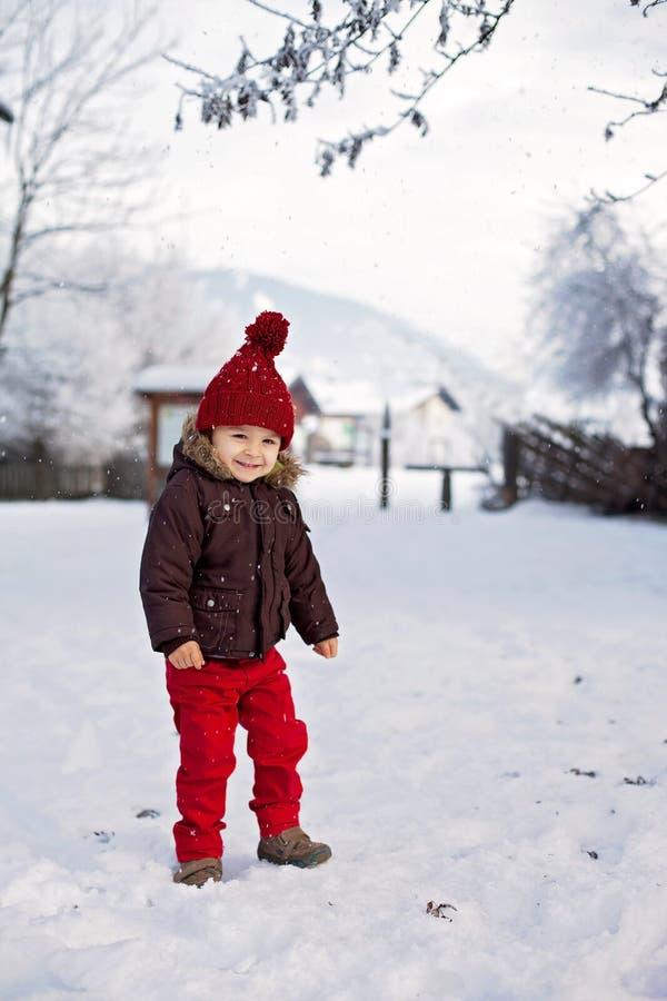 El retrato del niño en chaqueta marrón y rojo hizo punto el sombrero y el tr rojo fotografía de archivo