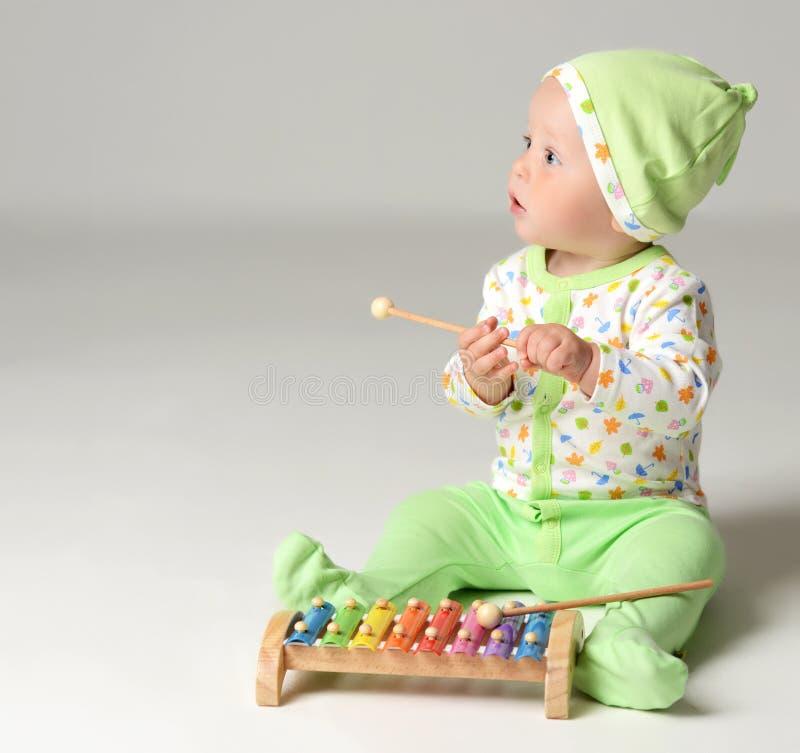 El retrato del niño infantil del niño del bebé del niño que se sienta en cuerpo verde claro y el juego con el xilófono juegan fotografía de archivo