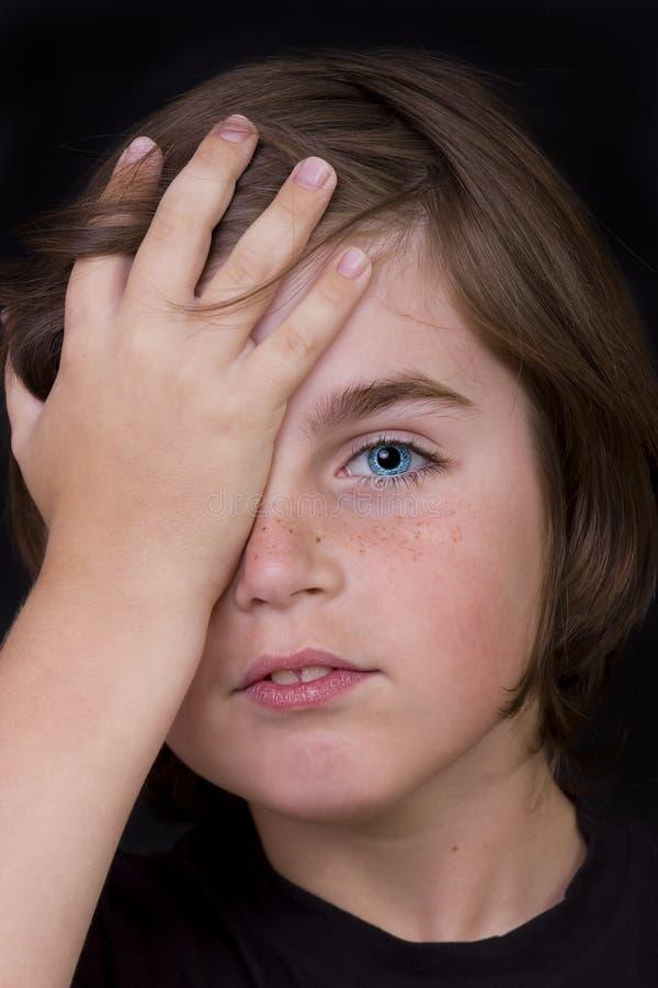 El retrato del niño pequeño lindo cerró un ojo con su mano fotografía de archivo