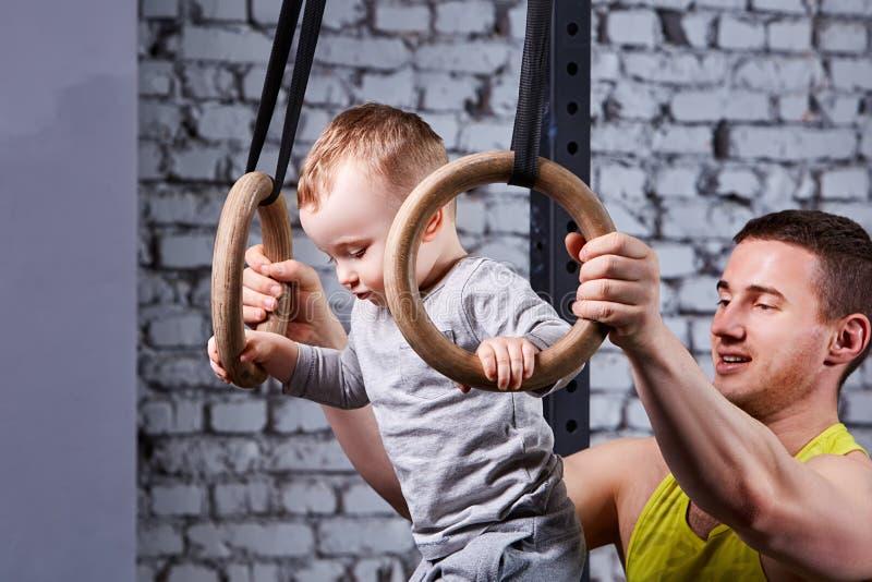 El retrato del padre joven feliz entrena al pequeño hijo con los anillos gimnastic contra la pared de ladrillo en el gimnasio foto de archivo