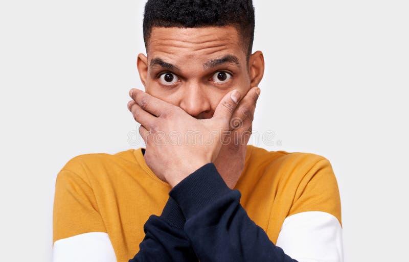 El retrato del primer de la boca africana horrorizada chocada de la cubierta del hombre joven con las manos siente asustado miran imagenes de archivo