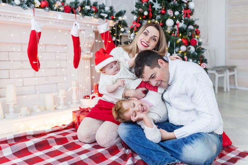 El retrato del primer de la familia alegre linda cerca del árbol de navidad en casa, los padres felices con los niños celebra día foto de archivo
