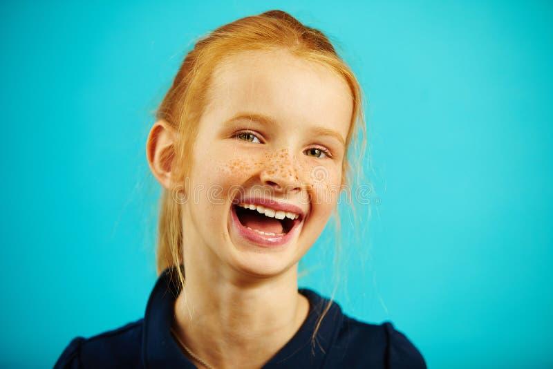 El retrato del primer de la muchacha de risa alegre con el pelo y las pecas rojos en azul aisló el fondo Niño feliz foto de archivo