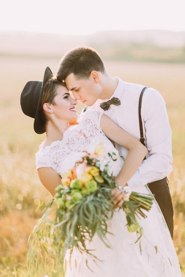 El retrato del primer de los recienes casados que se colocan comparativos el uno al otro mientras que los novios están abrazando  fotografía de archivo libre de regalías