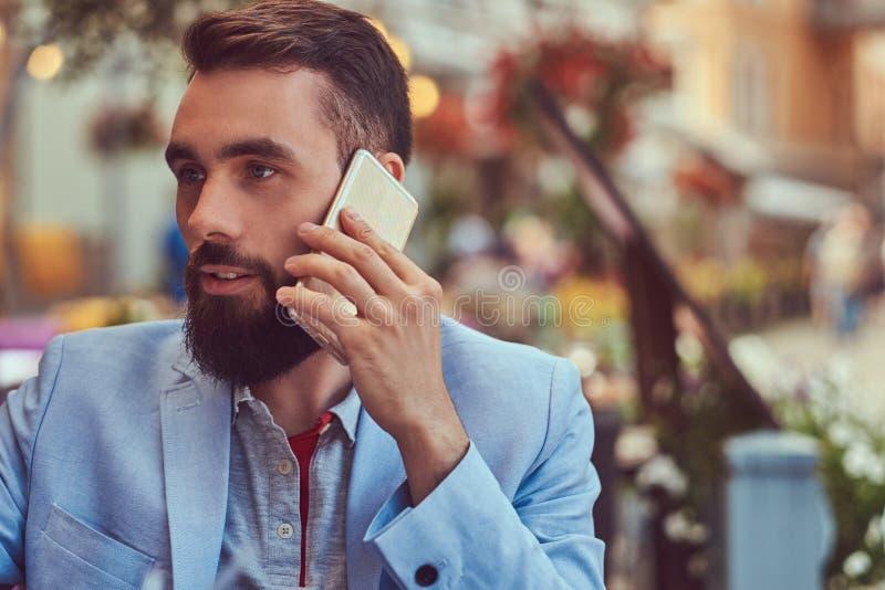 El retrato del primer de un hombre de negocios barbudo de moda con un corte de pelo elegante, hablando por el teléfono, bebe un v fotos de archivo