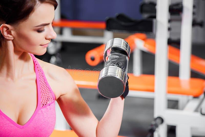 El retrato del primer de una mujer joven que hace pesa de gimnasia ejercita en el gimnasio imagen de archivo libre de regalías