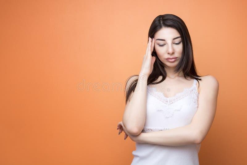 El retrato del primer de una mujer pensativa morena hermosa joven que lleva a cabo su mano nueva su cabeza y que mira abajo, pien fotografía de archivo libre de regalías
