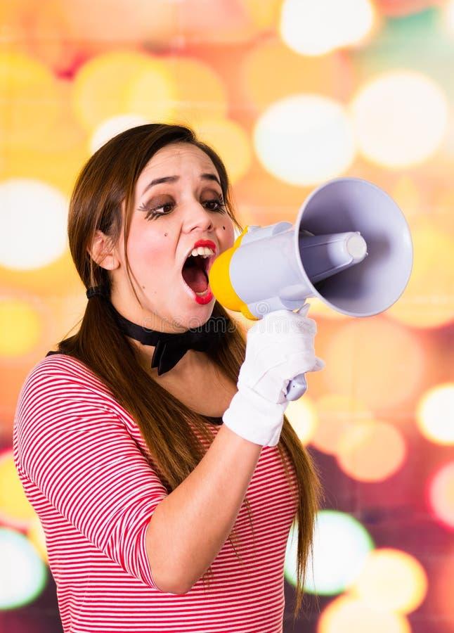 El retrato del primer del payaso de sexo femenino imita el griterío con un megáfono foto de archivo libre de regalías
