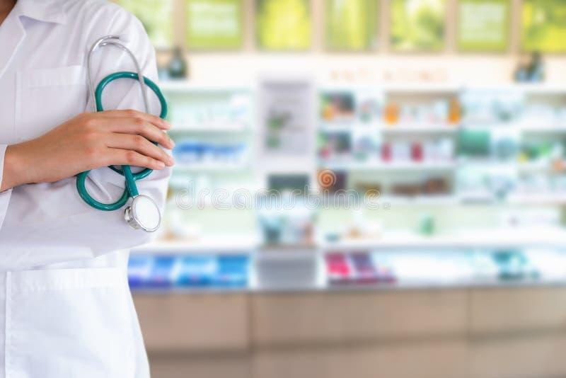 El retrato del primer del doctor Hand está sosteniendo el estetoscopio delante del fondo de la droguería, de la atención sanitari foto de archivo