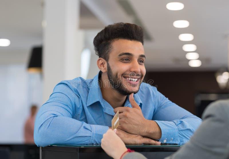 El retrato del primer del hombre de negocios sonriente feliz da la tarjeta de crédito al ayudante de tienda femenino Paying For C imagen de archivo libre de regalías