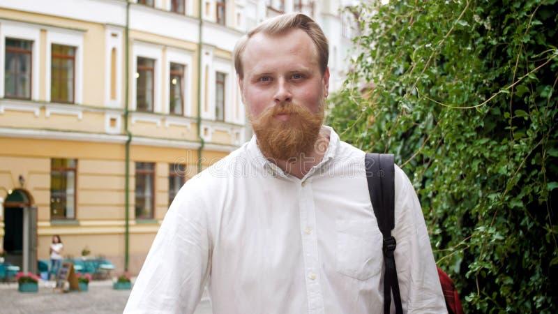 El retrato del primer del hombre joven sonriente con la barba roja que presenta en la calle en el sol irradia fotografía de archivo libre de regalías