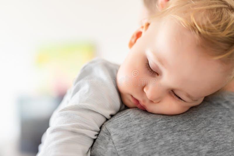 El retrato del primer del ni?o peque?o cauc?sico rubio adorable lindo que duerme en padres lleva a hombros dentro Sensaci?n dulce imágenes de archivo libres de regalías