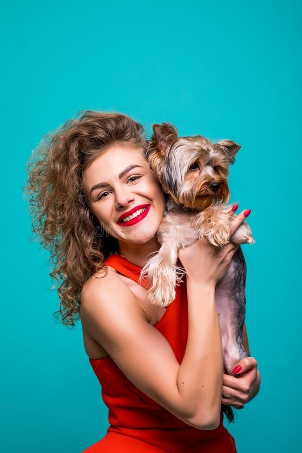 El retrato del primer del terrier de Yorkshire de abarcamiento sonriente de la mujer atractiva joven aisló vista delantera sobre  imagen de archivo libre de regalías