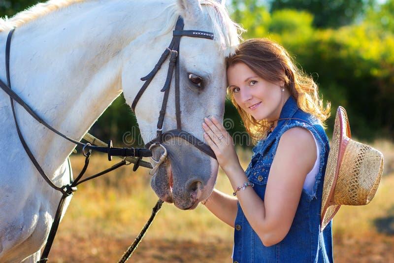 El retrato del ` s de la muchacha con el sombrero que abraza un caballo foto de archivo