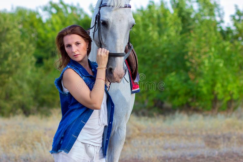 El retrato del ` s de la muchacha que abraza un caballo blanco foto de archivo libre de regalías
