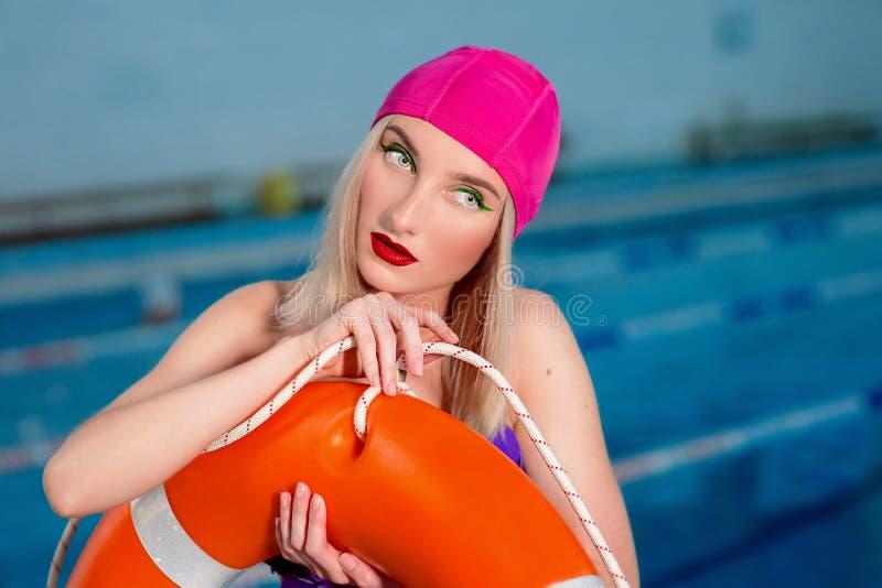 El retrato del salvavidas rubio atractivo hermoso atlético de la mujer con elegante compone en casquillos y bañador de la nadada fotografía de archivo