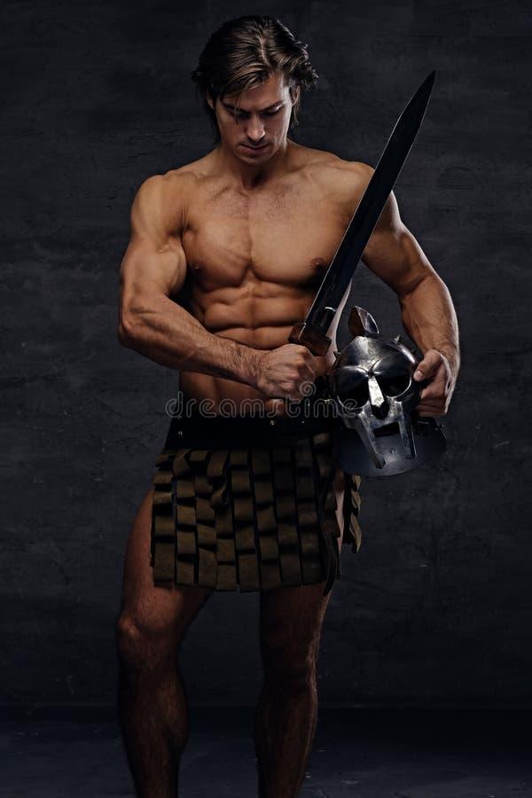 El retrato del varón muscular descamisado lleva a cabo el helme de plata del gladiador foto de archivo
