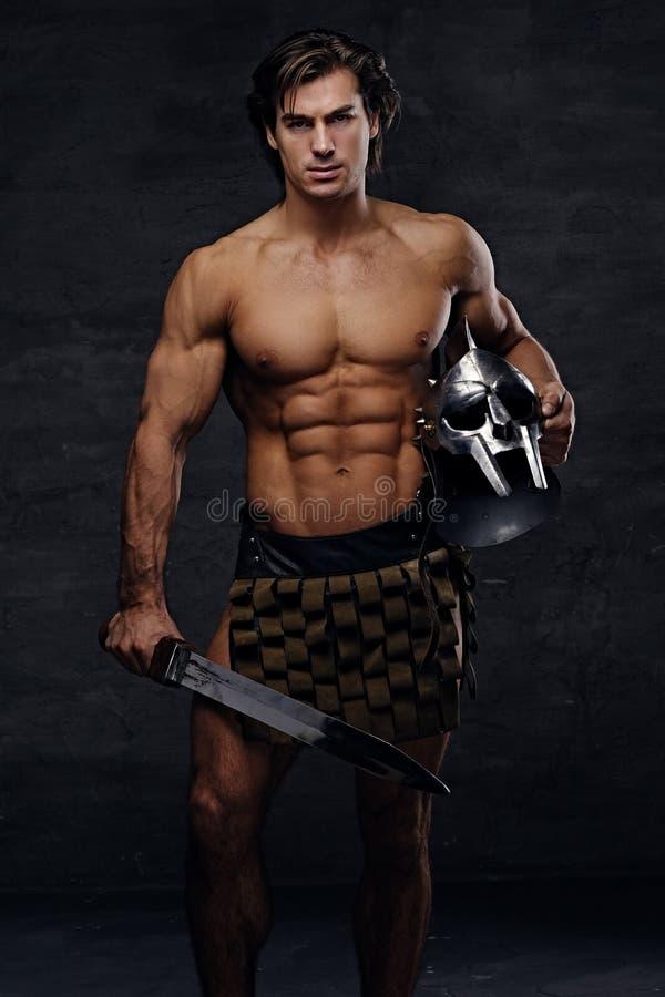 El retrato del varón muscular descamisado lleva a cabo el helme de plata del gladiador foto de archivo libre de regalías