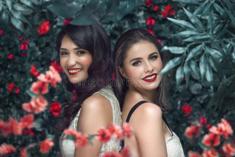 El retrato del verano de dos mujeres jovenes con las flores florecientes enrruella imágenes de archivo libres de regalías