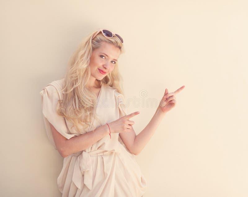 El retrato del verano de la mujer rubia hermosa joven en el vestido blanco que presenta cerca de la pared y se divierte Entonado  fotos de archivo libres de regalías