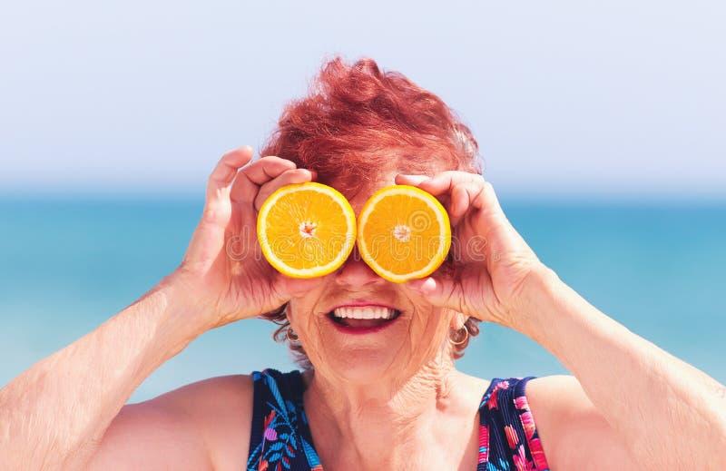 El retrato divertido de la mujer madura, abuela que se divierte con la naranja observa el vacaciones de verano imágenes de archivo libres de regalías