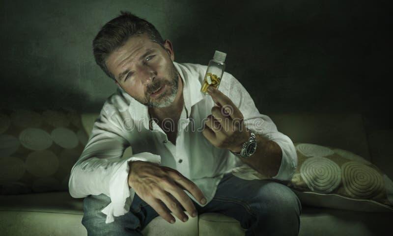 El retrato dramático de píldoras deprimidas y perdidas atractivas jovenes envicia al hombre que el antidepresivo de la tenencia h imágenes de archivo libres de regalías