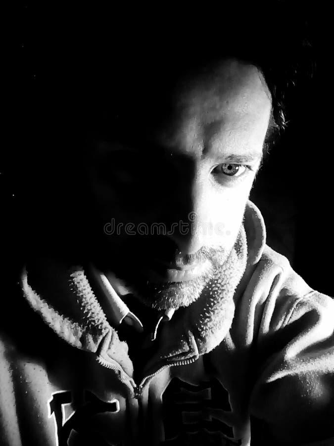 El retrato en la oscuridad - foto blanco y negro del hombre fotografía de archivo
