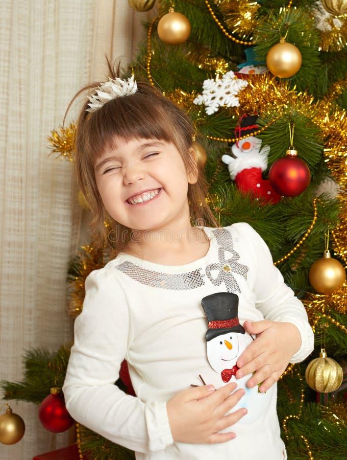 El retrato feliz de la muchacha en la decoración de la Navidad, jugando con el juguete del muñeco de nieve, concepto de las vacac fotografía de archivo