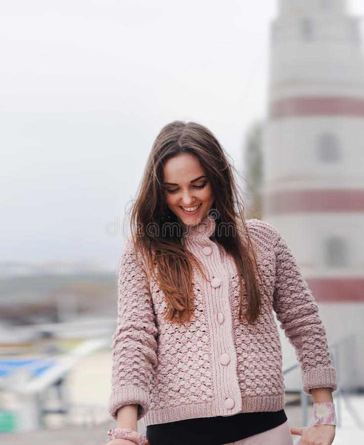 El retrato feliz joven de la mujer, mirando abajo y sonriendo, se vistió en el suéter rosado apacible lindo, moda del otoño fotografía de archivo libre de regalías